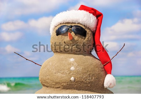 Snowman made out of sand against the sky. Holiday concept can be used for New Year and Christmas Cards - stock photo