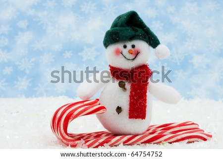 snowman on a candy cane sled with snow, Snowman having fun - stock photo