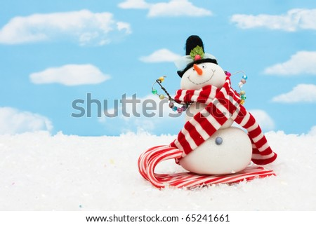 Snowman on a candy cane sleigh on a blue sky background, snowman having fun - stock photo