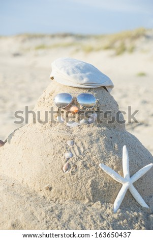 Snowman On Beach with shells as mouth and sun glasses - stock photo