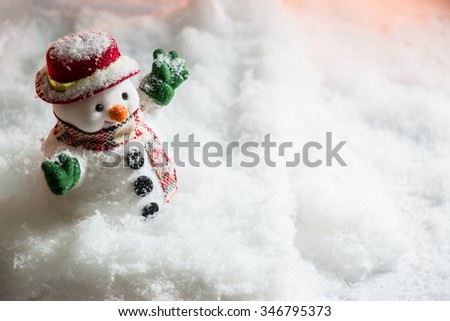 Snowman stand among pile of snow at silent night with a light bulb, light up the hopefulness and happiness in Merry christmas and new year night. - stock photo