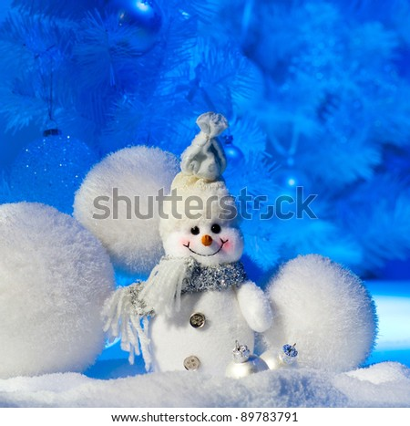 snowman under decorated christmas tree - stock photo