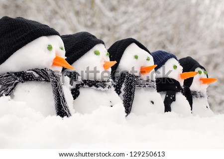 Snowmen close up in a row with hats and scarfs - stock photo