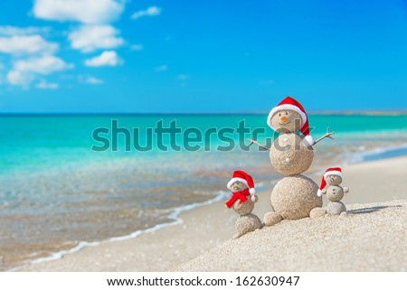 Snowmen family at sea beach in santa hats. New years and christmas holiday in hot countries concept. - stock photo