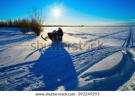 Snowmobile flies through a snowy field on a Sunny day . - stock photo