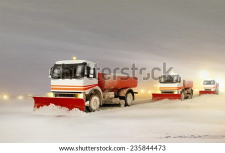 Snowplow Trucks Removing the Snow from the Highway during a Cold Snowstorm Winter Day  - stock photo