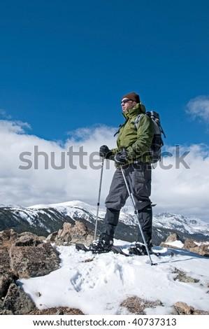 Snowshoer on a summit - stock photo