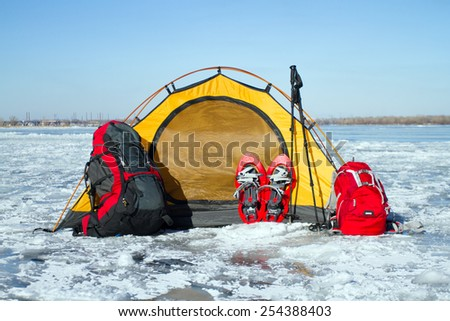 Snowshoes left in front of orange tent in winter forest - stock photo