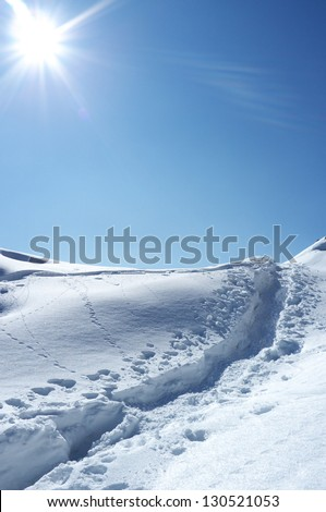 snowshoes traces in the snow on a sunny day - stock photo