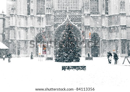 snowstorm in town: street scene with Christmas fir-tree and Cathedral - stock photo