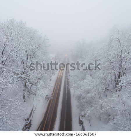 snowstorm, slick roads and lots of traffic in city - stock photo