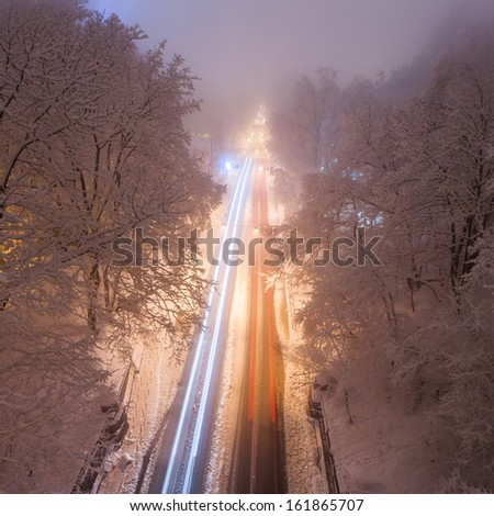 snowstorm, slick roads and lots of traffic in night city - stock photo