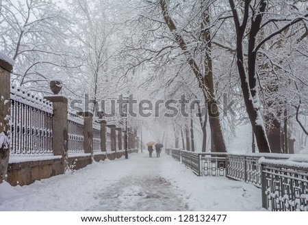 snowy city park and people with umbrellas - stock photo