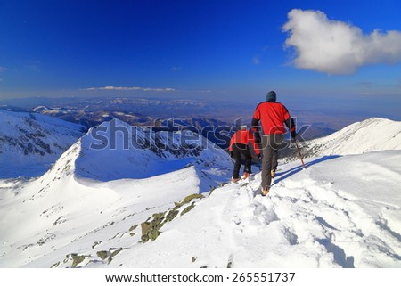 Snowy mountain and a team of hikers descending in sunny winter afternoon - stock photo