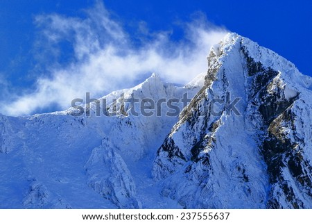 Snowy mountain peak under rare clouds during winter - stock photo