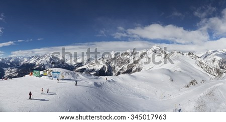 Snowy mountain top ski resort panorama. Start of a skiing slope with skiers. - stock photo