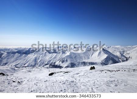 Snowy mountains at nice sun day. Caucasus Mountains, Georgia, ski resort Gudauri. Wide angle view. - stock photo