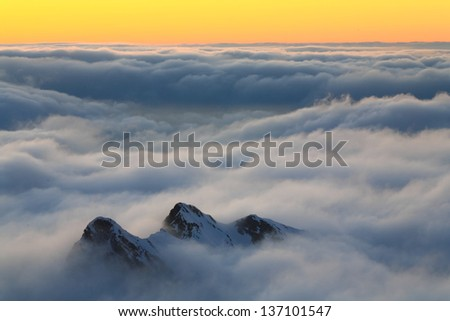 Snowy mountains at sunset, embedded by clouds - stock photo