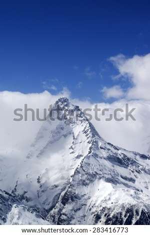Snowy mountains in clouds. Caucasus Mountains mount Belalakaya, ski resort Dombay. - stock photo