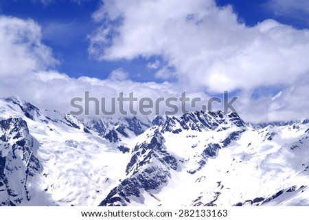 Snowy mountains in sun day. Caucasus Mountains, region Dombay. View from ski slope.  - stock photo