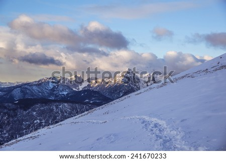 Snowy mountains on an early winter morning. Photograph was taken in Slovenia on the border with Austria. Panorama with forest, mountains, clouds and clear sky. - stock photo