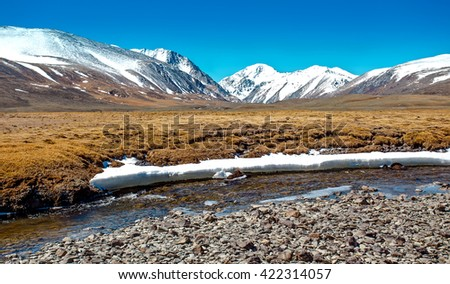Snowy mountains reflected in lake. Severe mountains peaks covered by snow. Russia, Siberia, Altai mountains, Chuya ridge. - stock photo