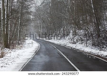 Snowy road in winter landscape - stock photo