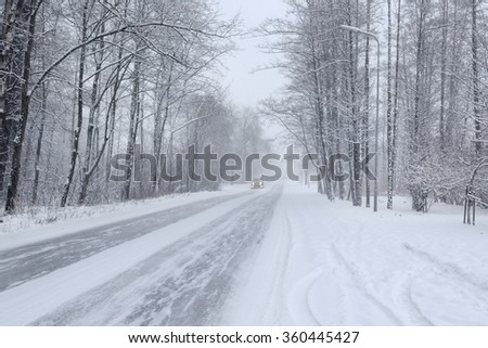 Snowy road in winter woods with a car - stock photo