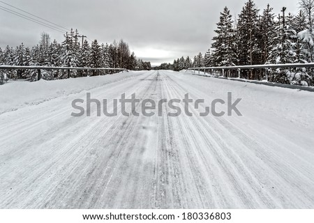 Snowy road with ice and trees in Sweden - stock photo