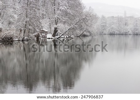 Snowy scene reflecting on the surface of the icy lake. - stock photo
