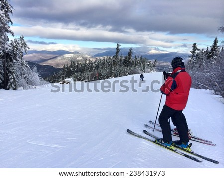 Snowy slope in the mountains with two skiers - stock photo