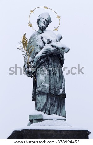 Snowy St. John of Nepomuk Statue on Prague Charles Bridge, Czech republic - stock photo