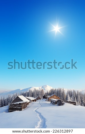 Snowy trail to the mountain village. Winter landscape with huts in the mountains. Carpathians, Ukraine, Europe - stock photo