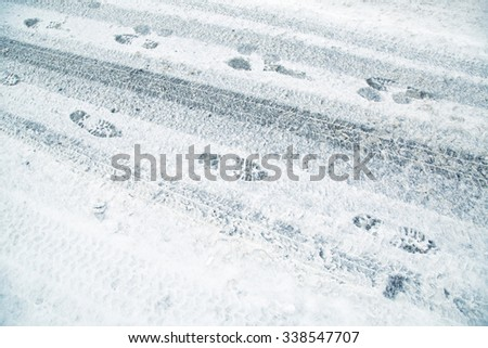 Snowy winter city asphalt road with tire trace and shoeprints. Danger icy and frozen city winter road background. - stock photo
