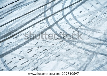 Snowy winter city road with tire trace and many footprints. - stock photo