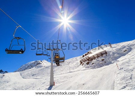 Snowy winter landscape and ski lift in the Alps - stock photo