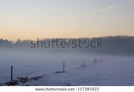 Snowy winter landscape in fog during sunset. - stock photo