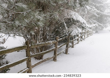Snowy winter landscape with rural wooden fence - stock photo