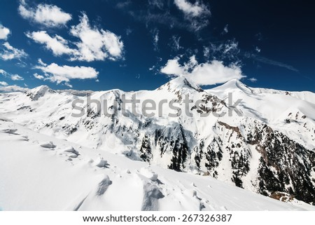 Snowy Winter Mountain Ridge and polarized sky with some clouds - stock photo