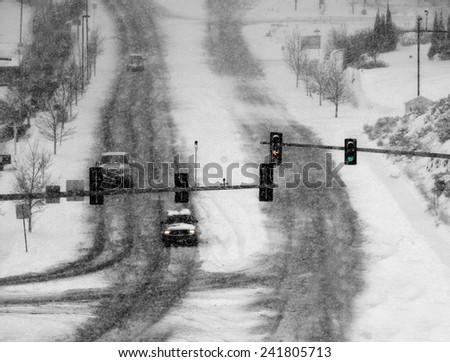 Snowy winter road with cars driving on roadway in snow storm and traffic lights - stock photo