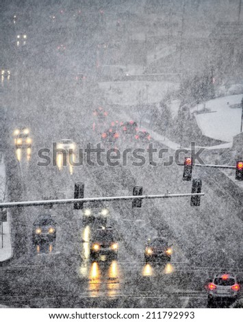 Snowy winter road with several cars driving on roadway with traffic lights - stock photo