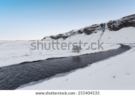 Snowy Winterscape with Stream, Mountain and Blue Sky - stock photo