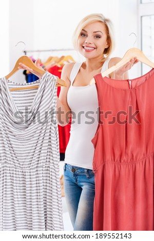 So hard to choose! Attractive young blond hair woman holding two dresses and looking at camera - stock photo