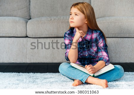 So many questions. Pensive little girl holding book and looking thoughtful while sitting on the carpet in lotus position at home - stock photo
