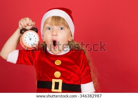 So much to do so little time. Little girl wearing Christmas outfit screaming with surprise holding clock in her hand - stock photo