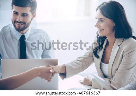 So nice to meet you! Close-up part of young beautiful women shaking hands with smile while sitting at the office table with her coworkers - stock photo