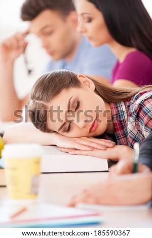 So tired of studying. Beautiful female student sleeping while sitting at the desk with other students - stock photo