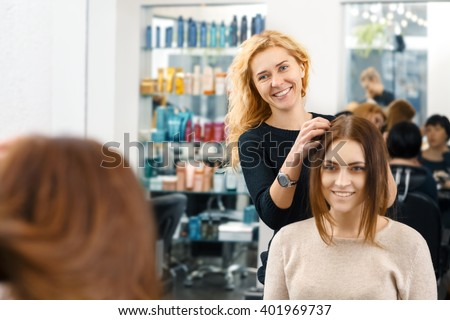 So what are we going for? Cheerful hairdresser working with her client at the beauty salon - stock photo