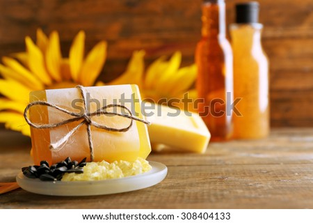 Soap bar and Spa treatments and sunflower on wooden background - stock photo
