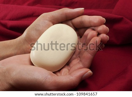 Soap bar in two hands red background - stock photo